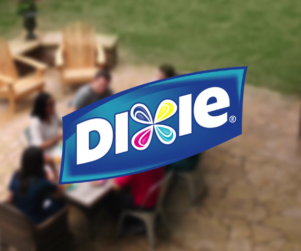 Dixie paper products logo superimposed over a family eating outside in their backyard