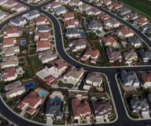 Aerial view of a neighborhood of houses with a Discovery Channel bug in the bottom right corner