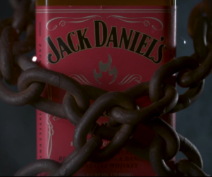 Close up of Jack Daniels Tennessee Fire whiskey bottle label with metal chains wrapped around it.