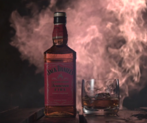 A bottle of Jack Daniel's Tennessee Fire Whiskey and a glass filled with whiskey on a table with a burst of fire in the background
