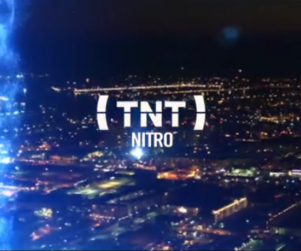 Aerial view of a city at night with a blue streak of light on the left side of frame. TNT Nitro logo in center of frame