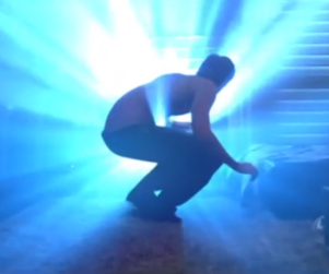 Man crouched in front of a wall with a bright blue light shining through it