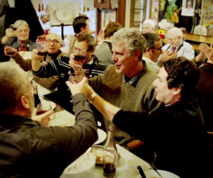 CNN original content host Anthony Bourdain toasting with a group of men inside a restaurant