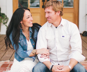 HGTV Fixer Upper hosts Chip and Joanna sitting on a porch smiling