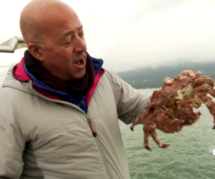 Travel Channel Bizarre Foods Host Andrew Zimmern on a boat holding a large crab